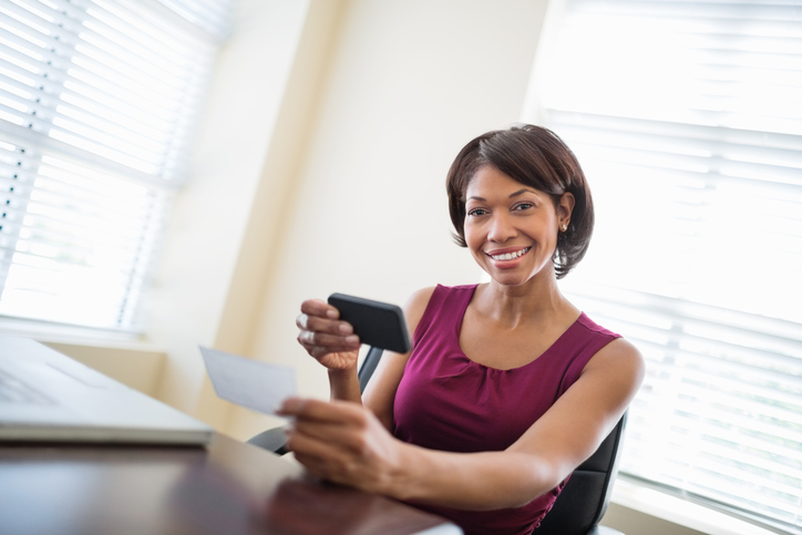 Portrait of MidAdult Woman with Smart Phone Depositing Check
